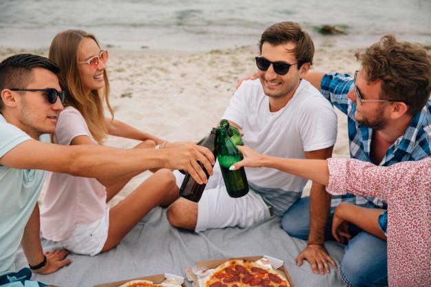grupo-de-melhores-amigos-fazendo-um-brinde-bebendo-cerveja-enquanto-se-diverte-na-praia_8353-6890
